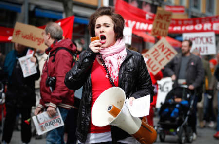 Young girl shouting into a megaphone during a protest